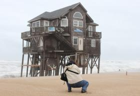 A picture of a woman photographing a beach house on stilts.