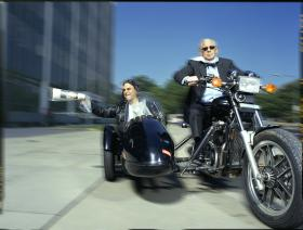 Carl Kasell and Peter Sagal (delivering news by sidecar)