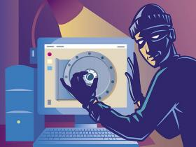 An internet hacker dressed as a robber cracks a code on a desktop