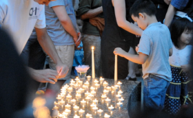 A child lays a candle around a fountain in memory of Dr. Feng Liu