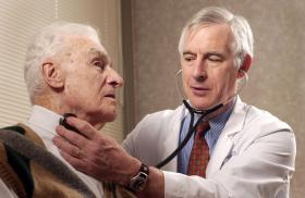 A Duke doctor examines an elderly patient.