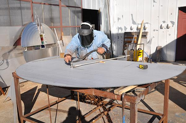 A worker plasma cutting the arch from stainless steel.
