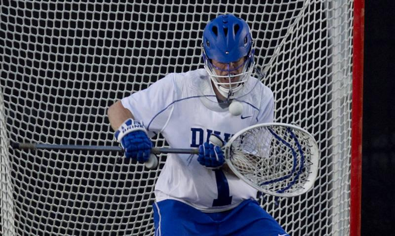 A Duke Blue Devil guarding the net in a lacrosse game against Virginia.