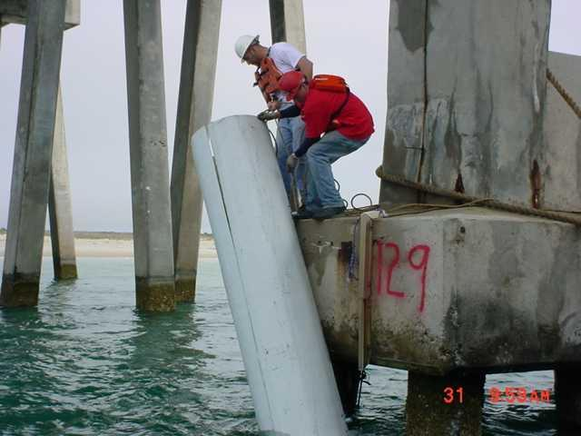 Workers lower a pile jacket to a diver in Oregon Inlet to place around one of the bridge's pilings.