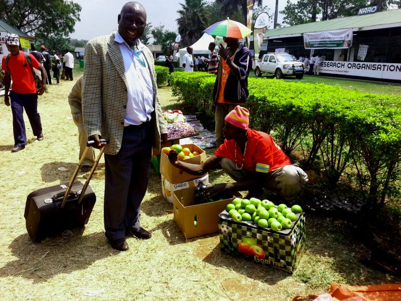 A man sells apples at a market in Uganda. Apples sell for about a dollar apiece.