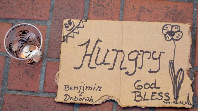 A homemade solicitation sign and cup, panhandling.