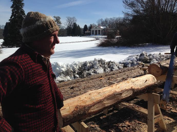 Carpenter Langley Freeauf stands near a recently hewed log. The James and Dolly Madison mansion is in the background.