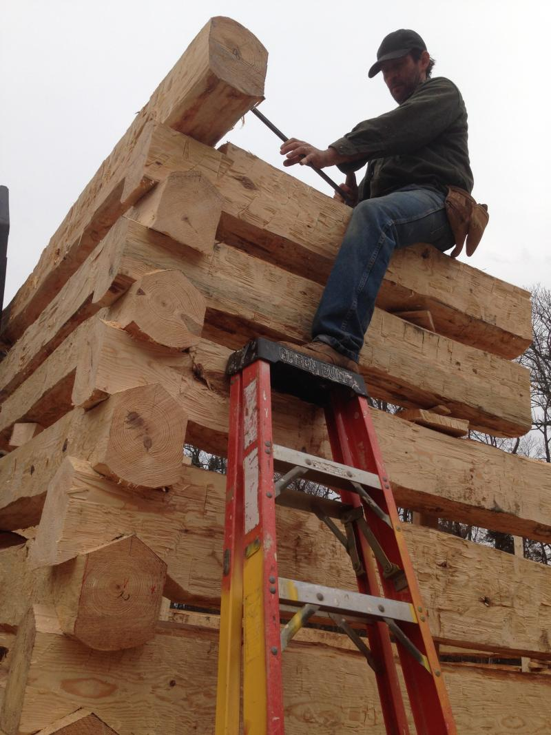 Participant Chris Kerr balances on top of the structure.