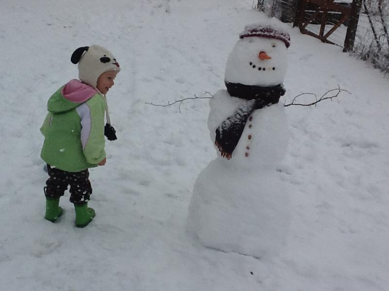 Wren in Durham admires a snowman she and some neighbors made.