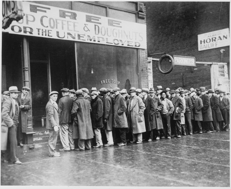 Men stand in line to receive free coffee and donuts for the unemployed - depression-era photograph