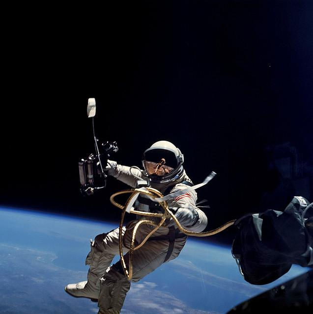 Ed White performs the first U.S. spacewalk. White floats in space with astronaut suit and attached to the shuttle by a cord. Earth is in the background.