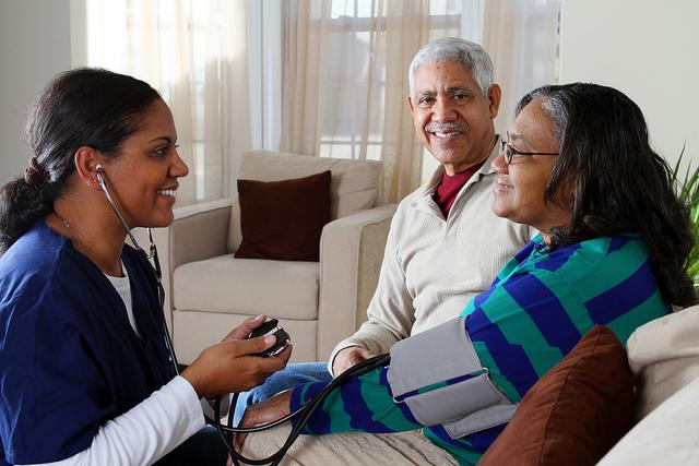 Nurse checking woman's blood pressure while family member watches