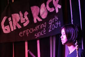 A photo of a girl near a Girls Rock poster.