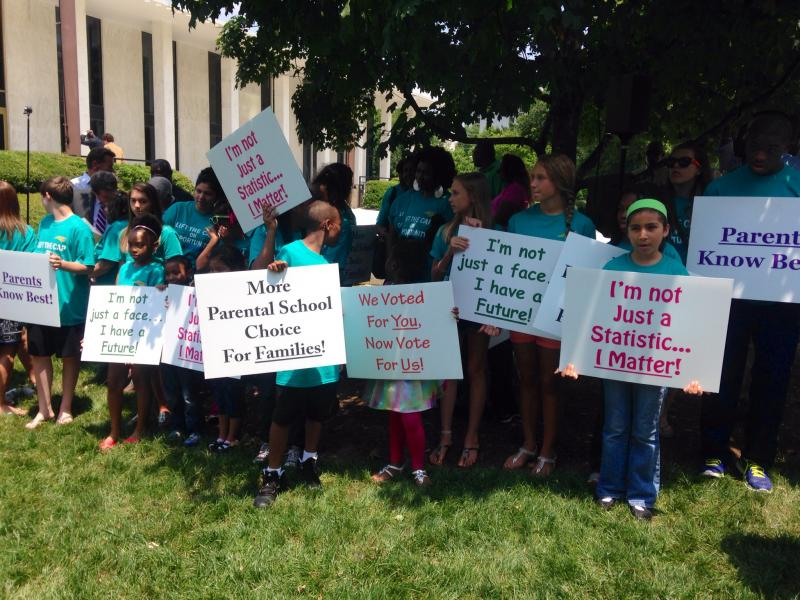 Parents, advocates and families gathered outside the legislative building on Tuesday to show their support for the state's private school voucher program.