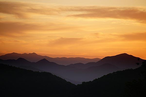 A picture of the sun setting behind the Blue Ridge Mountains.