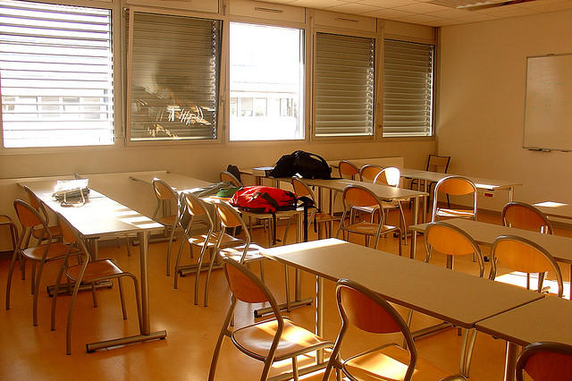 Photo: Desks and book bags in a classroom