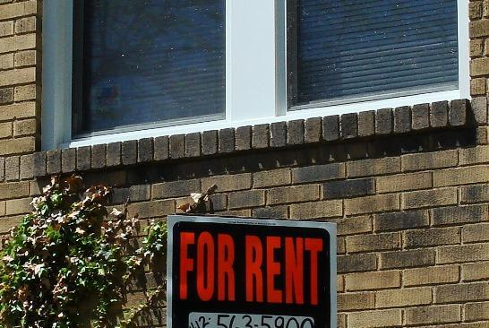 A picture of a window with a for rent sign.