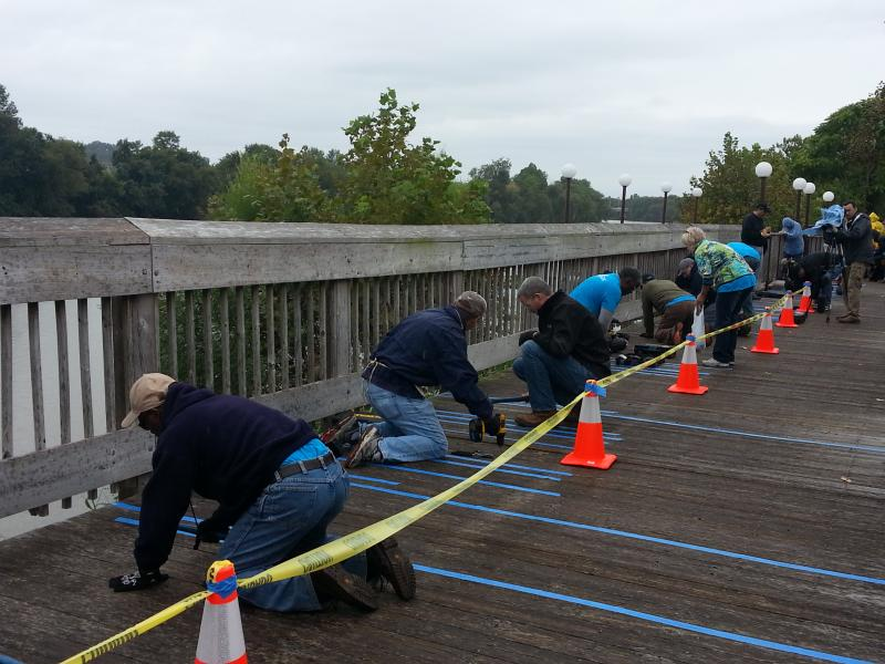 Duke Energy workers hammered and drilled along the Dan River boardwalk Wednesday morning.