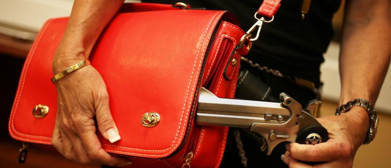 A picture of a handgun being pulled from a purse.