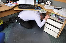A picture of a man taking cover under his desk.