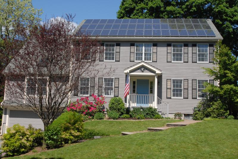 A picture of a house with solar panels on the roof.