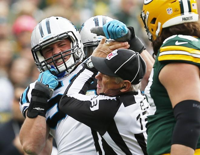 A picture of Luke Kuechly struggling with referee.