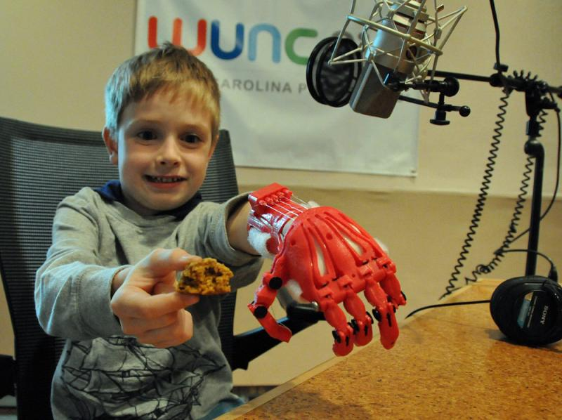 Holden Mora shows his new hand, and a pumpkin spice cookie.