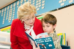 State Superintendent June Atkinson listens to a second grade student from Perquimans Central School read from his favorite book.