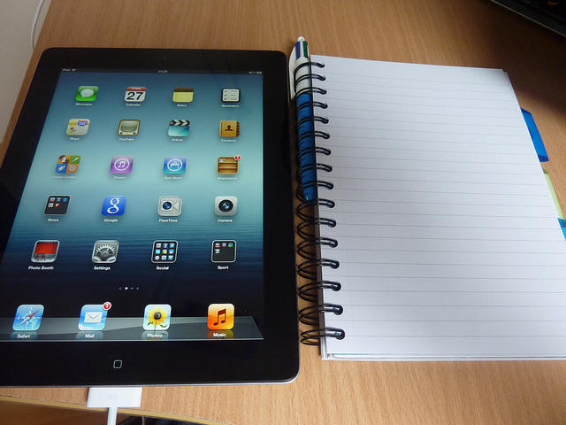 iPad with a notebook next to it