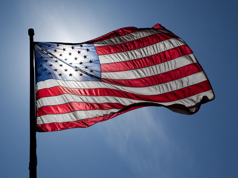 Flag of the United States of America, backlit, windy day.