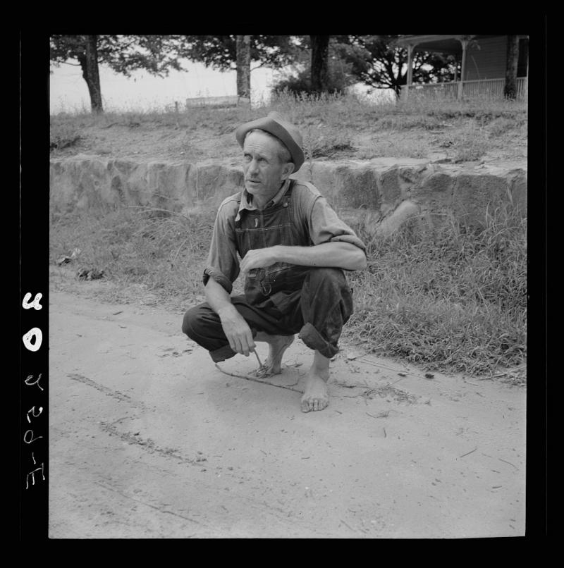 Roadside meeting with Durham County farmer. North Carolina. He gives road directions by drawing the dirt with a stick. July 1939