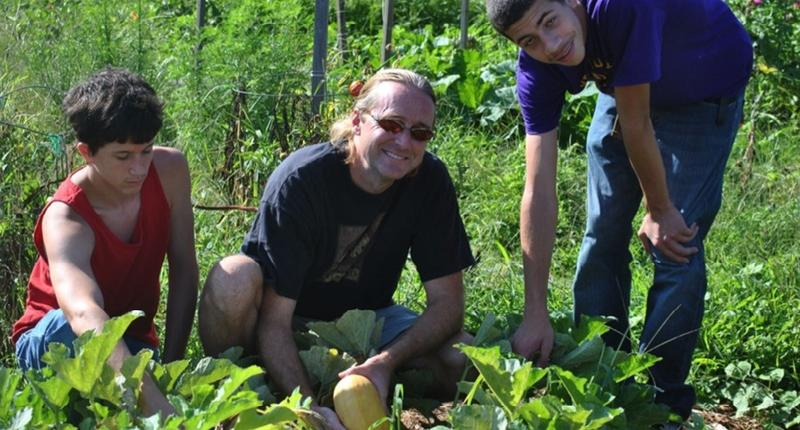 Image of three growingchange.org participants harvesting food.