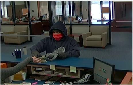 The bank robber is described as a light-skinned black male, approximately 20-35 years of age with a medium build.