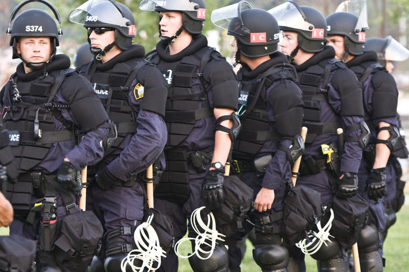 Saint Paul, Minnesota police officers covered in riot gear march and line up during the 2008 Republican National Convention (RNC) at the Xcel Energy Center.