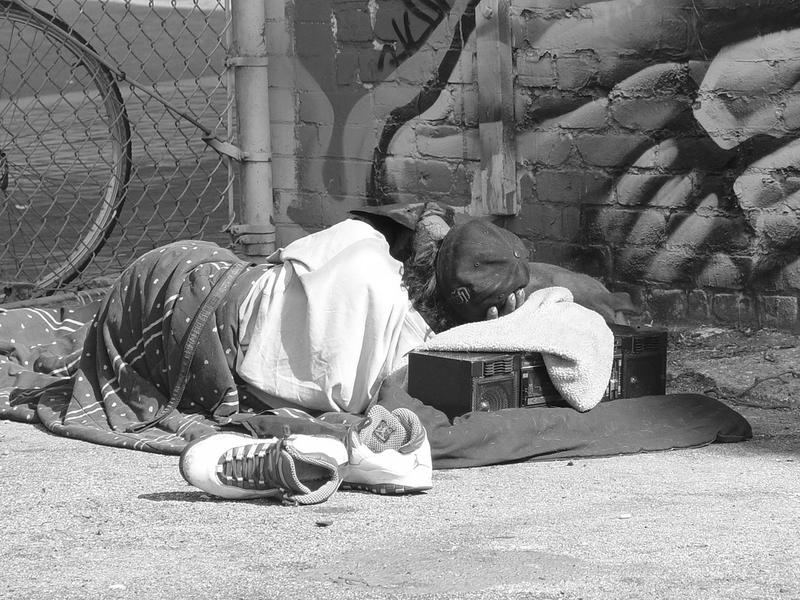A picture of a homeless person sleeping on the street.
