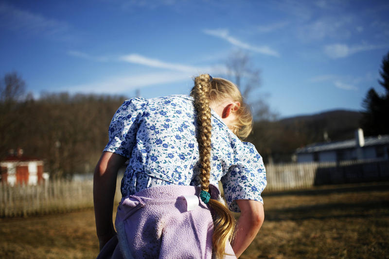 Rachel Hartzler, 7, takes a minute in between sessions of playing tag behind the Sugar Tree Country Store during the Highland Maple Festival in McDowell, Highland County, Virginia.
