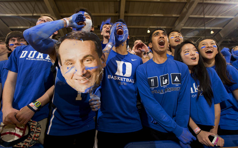 A picture of Duke fans holding a cutout of Mike Krzyzewski's face.