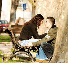 A picture of a couple at a bench.