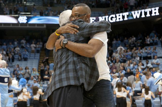Stuart Scott hugs coach Roy Williams.