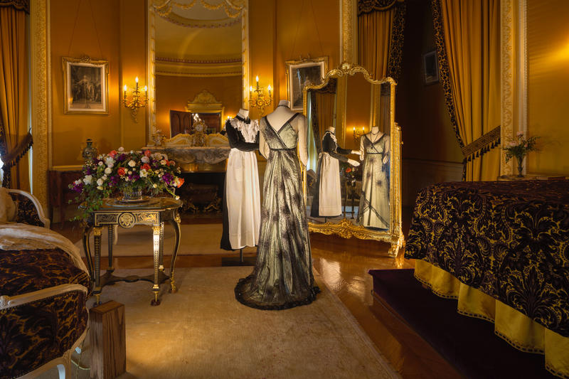 In Edith Vanderbilt's bedroom, Lady Mary Crawley is being dressed by her lady's maid in a green silk evening dress with black net overlay and black and silver starbursts, worn at dinner for Matthew's arrival at Downton.
