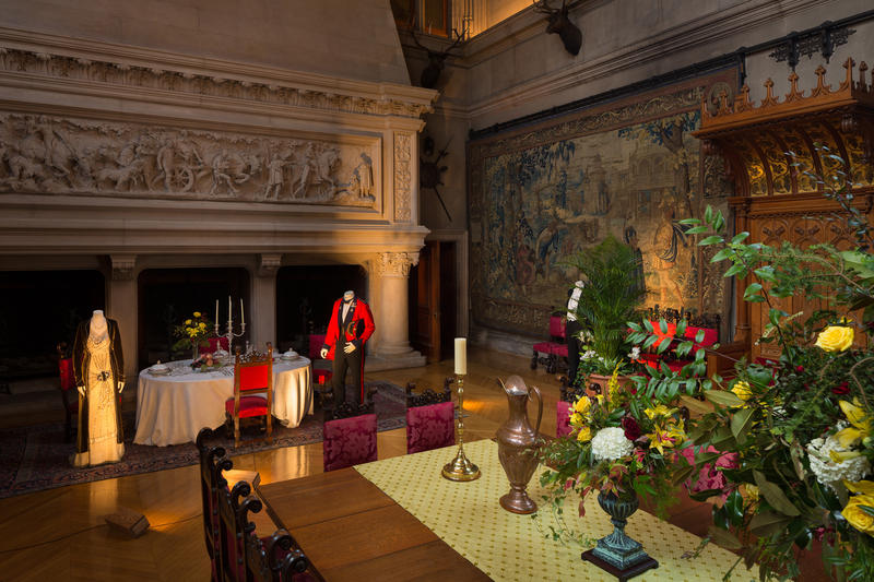 "Lord and Lady Grantham are located in the Banquet Hall of Biltmore House.  Lord Grantham's uniform with red jacket was based on a 1912 Indian Guides officer's uniform. Lady Grantham's dress was designed as a ""tea"" dress, worn for entertaining friends."