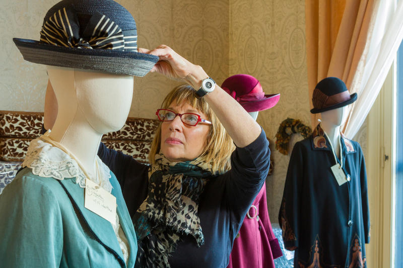 Costume expert Nancy Lawson tweaking the mannequins before the exhibit's opening.