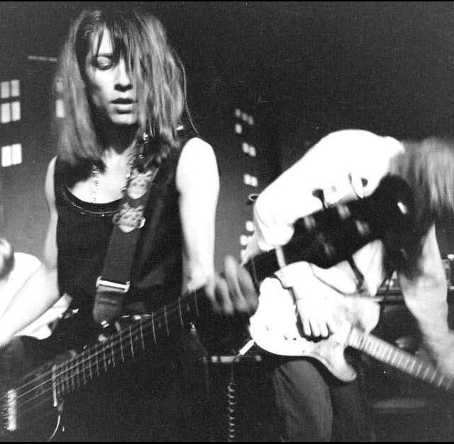 A picture of Kim Gordon playing guitar.