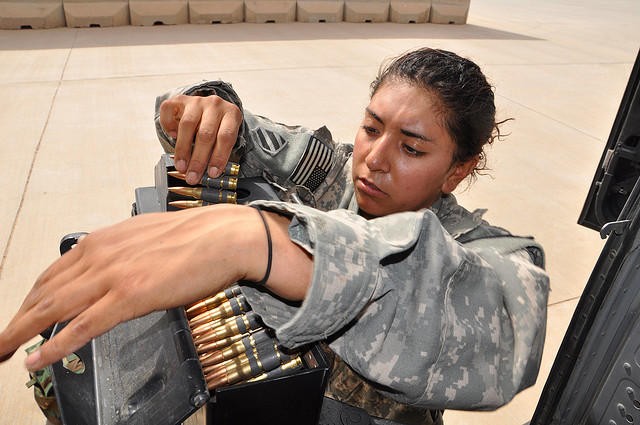 Spc. Crisma Albarran, of Orland, Calif., detaches an ammunition case from its mount after a UH-60 Black Hawk helicopter flight over Iraq, March 14, 2010.