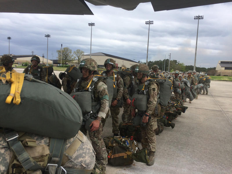 """A mixed """"chalk"""" of U.S. and British paratroopers line up to board a C-130 transport plane for the main jump of the joint exercise."""
