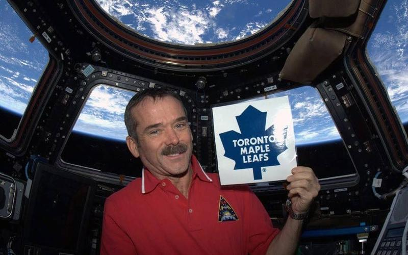 Canadian astronaut Chris Hadfield holds a Toronto Maple Leafs sign on a photo posted to his Twitter account. Professing his support for Toronto did not sit well with a number of hockey fans.