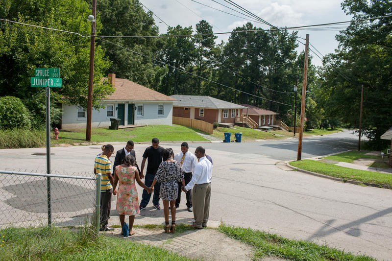 Locals, led by Pastor Sanders Tate of Mt. Gilead Baptist Church, pray for peace at an East Durham intersection at the beginning of the 2013 school year.