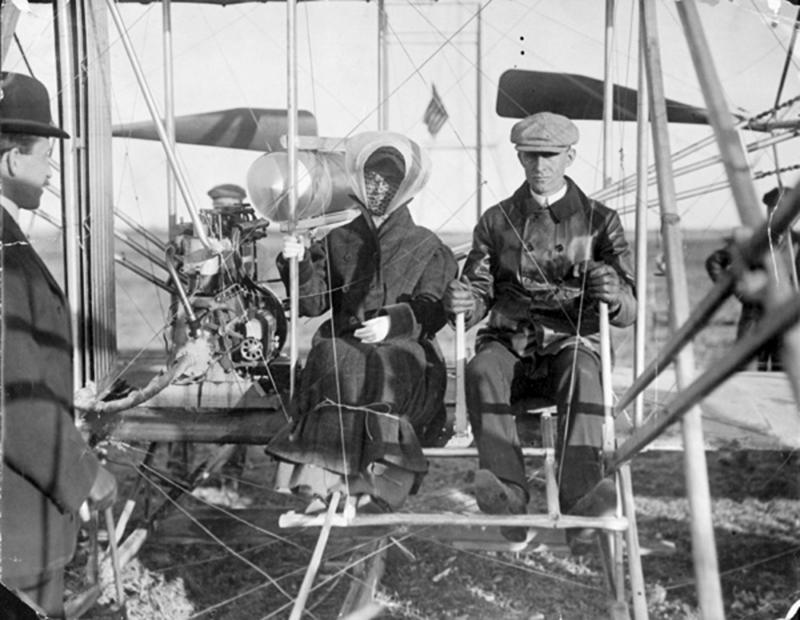Image of Katharine Wright sitting beside Wilbur before her first flight in 1909.