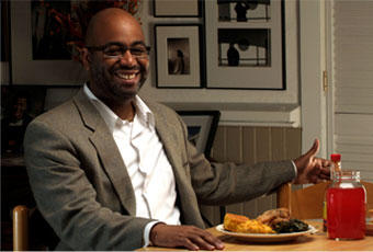 Image of Adrian Miller, a culinary historian, sitting with a plate of soul food.