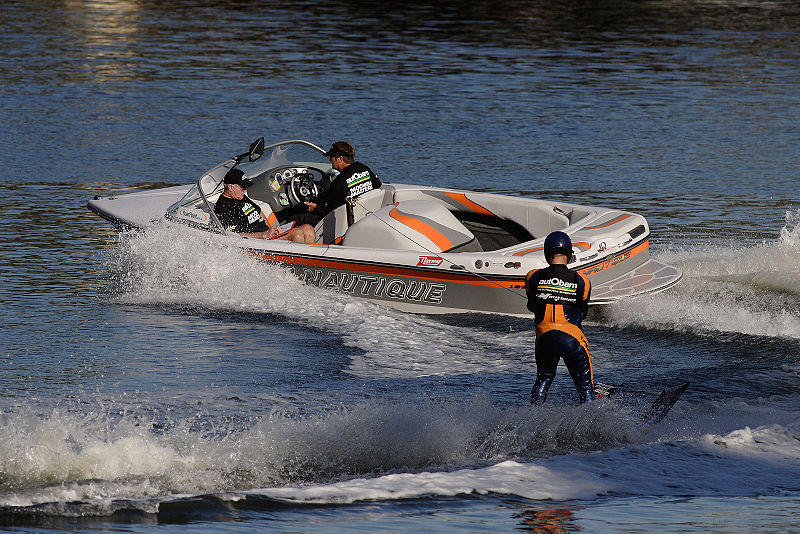 A picture of a motor boat pulling a water skiier.